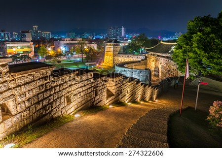 The old walls of Hwaseong Fortress lit up at night in Suwon, South Korea.