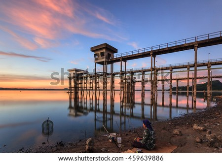 The old water supply station and fisherman. - stock photo