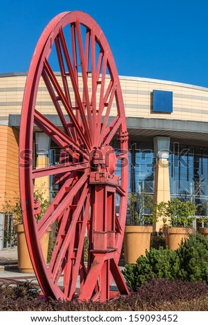 """The old wheel  of a mine shaft in front of the """"Silesia""""  shopping mall and entertainment center  in Katowice, Poland. The  complex was built on the site of a former coal mine. - stock photo"""