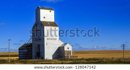 The old white Meacham grain elevator on the Canadian prairies. - stock photo
