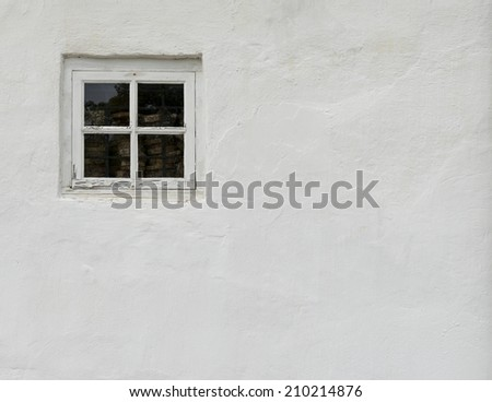 The old white plastered wall with a small window as background - stock photo