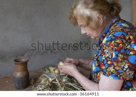 The old woman cuts an onions at itself in the house