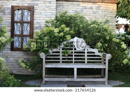 The old wooden bench near a house - stock photo