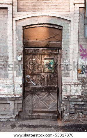The old wooden door in a brick house. The rusty mailbox. The door is closed the lock. - stock photo