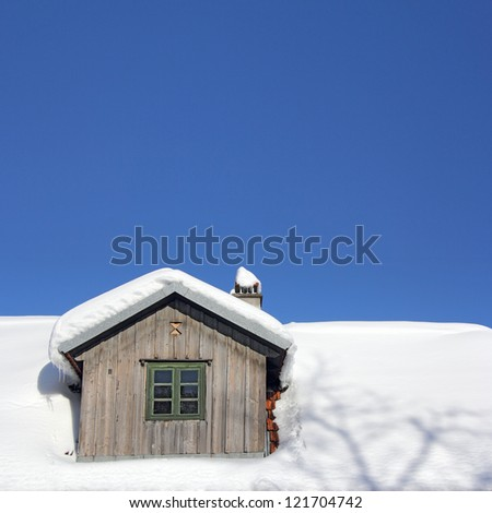 The old wooden roof covered with snow and blue sky
