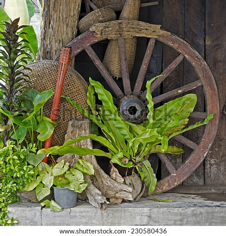 The old wooden wheel and  bamboo basket of tools in Thailand - stock photo