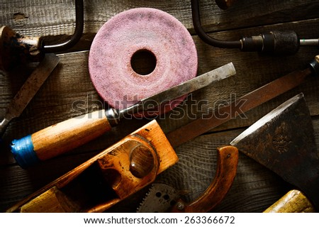 The old working tool. Many old working tools (axe, chisel and others) on a wooden background. - stock photo