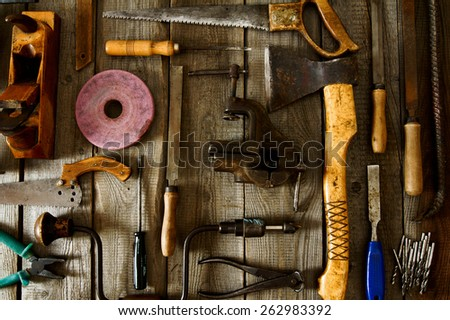 The old working tool. Many old working tools ( plane, saw and others) on a wooden background. - stock photo