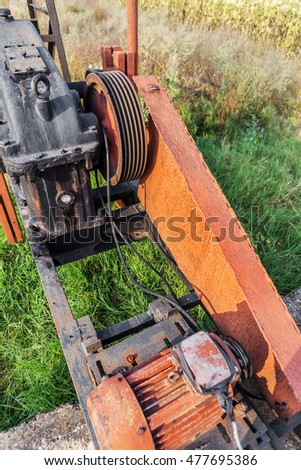 The old worn-out equipment oil rig. Old motor, belt drive, streaks of dirty engine oil in the worn-out equipment. Rusty metal