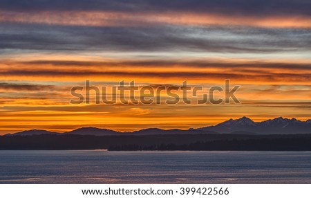The Olympic Mountains are Bathed in a Sea of Orange and Red in this Sunset Image from Seattle, Washington - stock photo