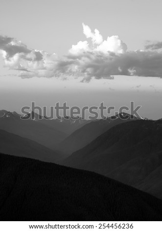 The Olympic Mountains stand against a dramatic sky at sunrise - stock photo