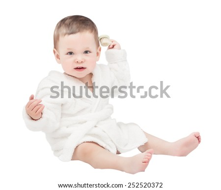 The one-year-old kid in a white dressing gown with a hairbrush in a hand