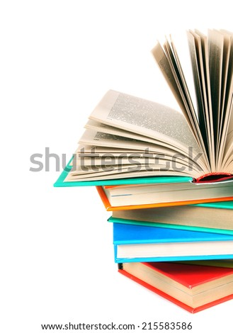 The open book on a pile of multi-coloured books. On a white background.