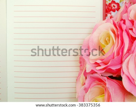 the open notebook paper with red lines and artificial roses flower - stock photo