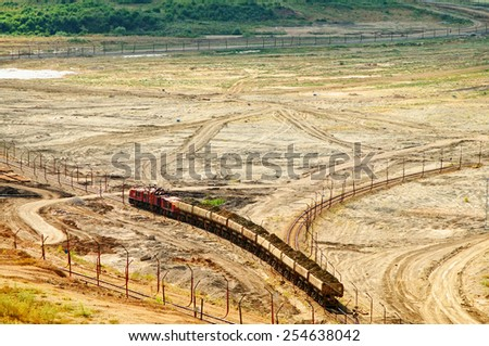 The open-pit mine, mining train carrying excavated materials at the forefront, view from above - stock photo