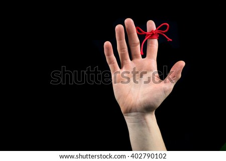 The open right hand with red reminder string tied to index finger isolated on black - stock photo