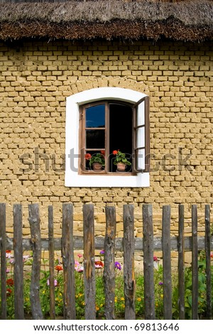 the open window with flower in pot on old house - stock photo