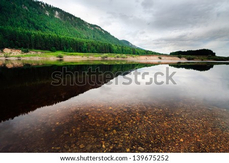 The opposite coast reflected in silent water of the river in rainy weather, Sakha (Yakutia) Republic, Eastern Siberia, Russia - stock photo