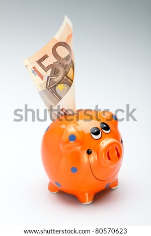 The orange money box costs on a white and gray background with denomination of money, series different banknotes with different values - stock photo