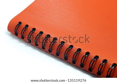 The orange notepad book with black clip