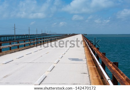 The original Seven Mile Bridge is a converted railroad bridge after the the railroad ceased in 1935. The handrails are the actual original rails. - stock photo