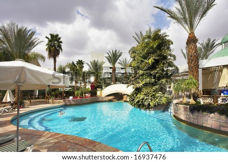 The ornate pool in an environment of palm trees, awnings and beach plank beds