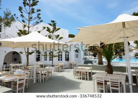 The outdoor restaurant near swimming pool at luxury hotel, Santorini island, Greece - stock photo