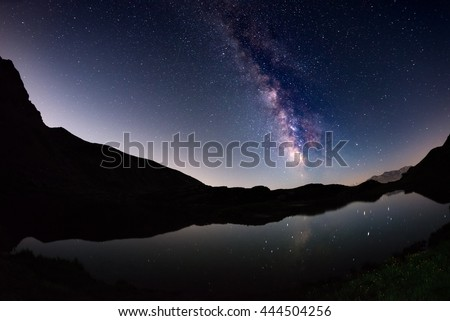 The outstanding beauty of the Milky Way arc and the starry sky reflected on lake at high altitude on the Italian Alps, Torino Province. Fisheye scenic distortion and 180 degree view. - stock photo