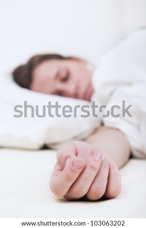 The outstretched hand of a sleeping woman lies on the mattress, the face of the brunette woman out of focus in the background - stock photo