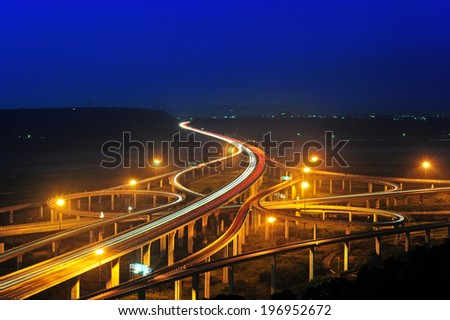 The overpasses wind around one another as they are lit up at night. - stock photo