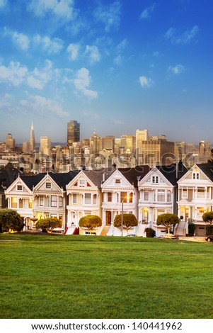 The Painted Ladies of San Francisco, California sit glowing amid the backdrop of a sunset and skyscrapers. - stock photo