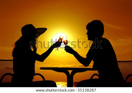 The pair silhouette is held by goblet with wine on a sundown - stock photo