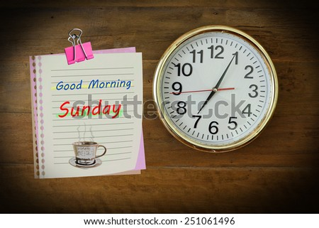 The paper wrote Good Morning Sunday with seven o'clock hanging on the wooden wall. - stock photo