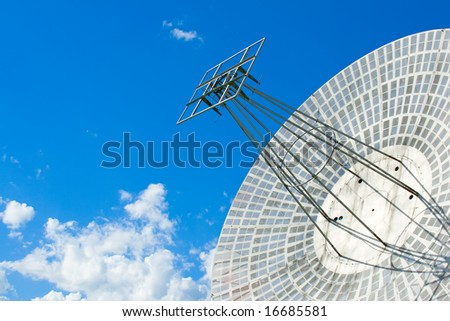 The parabolic antenna on a background of the blue sky - stock photo