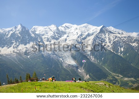 The paragladers prepare for flying against Massif du Mont-Blanc - stock photo