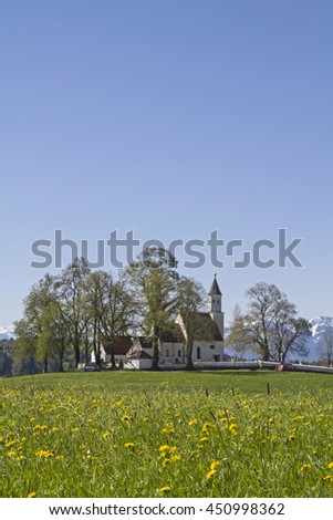 The parish church of Dietramszell is located between the idyllic meadows on a hill - stock photo