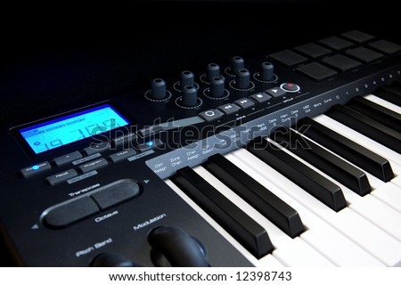 The Part of Professional MIDI-keyboard with blue screen on black background - stock photo