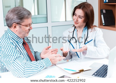 The patient and his doctor in medical office - stock photo