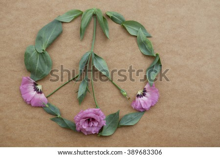 the peace sign on a natural background, flowers Lisianthus with stems and leaves beige background - stock photo
