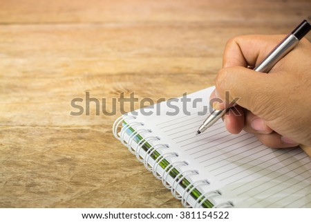 The pen is hand writing on the notebook. - stock photo