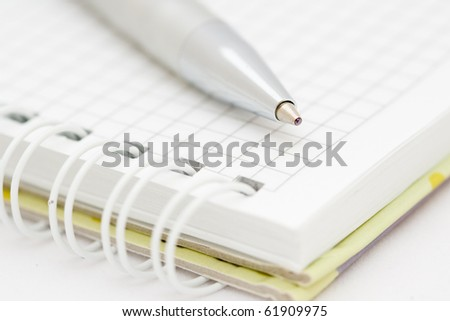 The pen lying on a notebook on a white background - stock photo