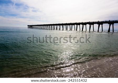 The Pensacole pier with the sun shining through - stock photo