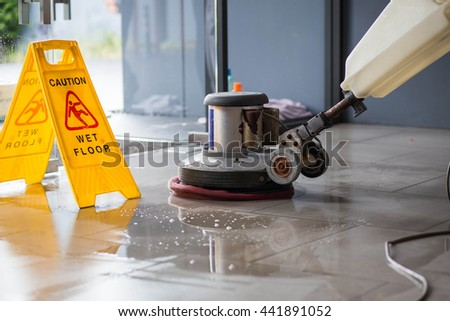 The people cleaning floor with machine. - stock photo