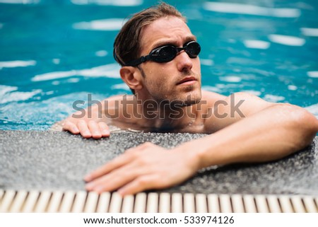 The perfect day for a swim. Serious male swimmer resting at the side of the pool