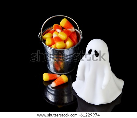 The perfect ghost with a bucket of candy corn and reflection - stock photo