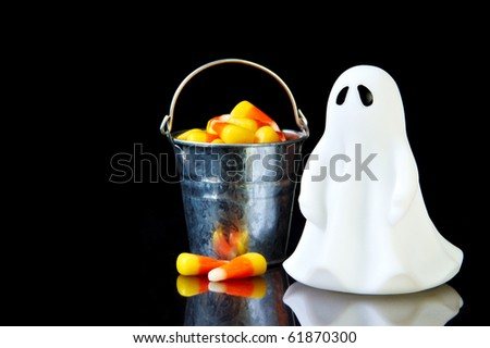 The perfect ghost with a bucket of candy corn and reflection