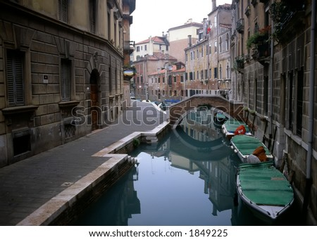 The perfect stillness of this canal in Venice, Italy, creates a mirrorlike reflection of the quaint buildings that line it. - stock photo