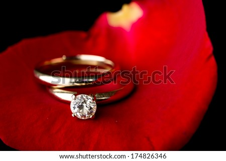 The perfect Valentine's Day gift, an engagement ring on a red rose - stock photo