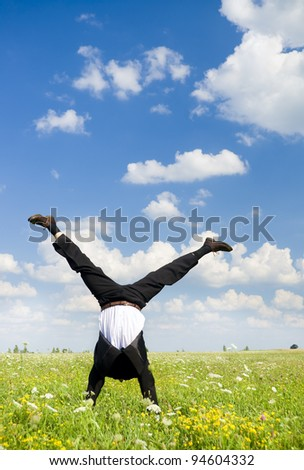 The person in a business suit costs on hands in the field - stock photo