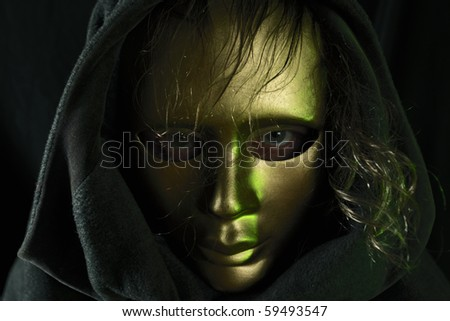 The person in a gold mask,green light. - stock photo